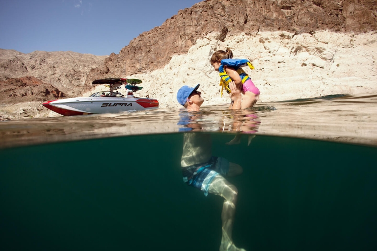 guy swimming with his daughter next to a supra boat